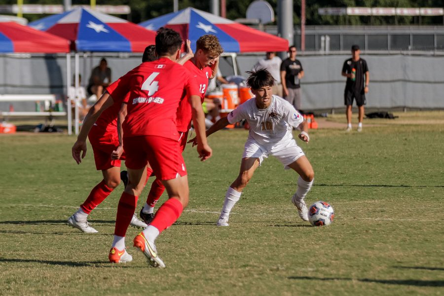Sport and leisure studies senior and forward Toi Yamaoka works to send the ball to his teammates while dealing with pressure from Simon Fraser players.