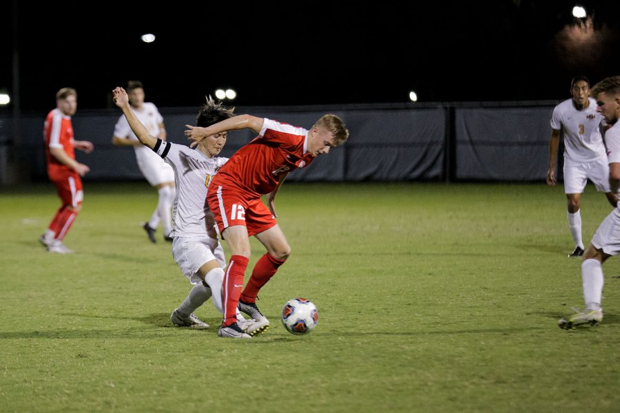 Sport and leisure studies senior and forward Toi Yamaoka kicks the ball from in between an opposing Rogers State player