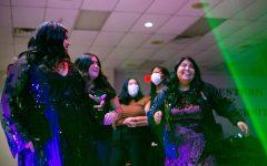 English senior Veronica Flores and biology with chemistry minor senior Estafani Vasquez dance with friends among the flashing lights at Noche de Estrellas.