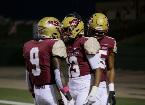 After making the first touchdown of the game, sports and leisure senior and wide receiver Kandin Robertson is congratulated by sports and leisure redshirt freshman and wide receiver JaJuan Mason and exercise physiology senior and running back Trenton Kennedy.