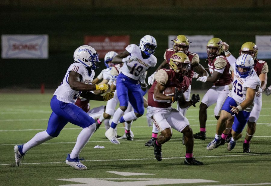Kinesiology senior and running back KVonte Jackson avoids pressure from Texas A&M Kingsville players.